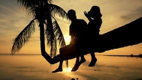 Η σκιαγραφία του νέου ευτυχούς πατέρα με την κόρη του κάθεται σε έναν φοίνικα κατά τη διάρκεια του καταπληκτικού χρυσού ηλιοβασιλ φιλμ μικρού μήκους