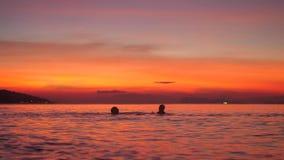 Η σκιαγραφία του πατέρα και λίγου γιου που λούζουν στη θάλασσα στο όμορφο ηλιοβασίλεμα και που κυματίζουν με το τους παραδίδει σε φιλμ μικρού μήκους