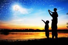 Η σκιαγραφία του σημείου χεριών χρήσης πατέρων ο γιος του εξετάζει τη πανσέληνο Στοκ εικόνα με δικαίωμα ελεύθερης χρήσης
