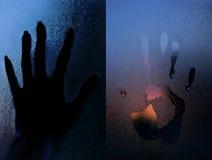 Η σκιαγραφία του χεριού επάνω το γυαλί στοκ εικόνα