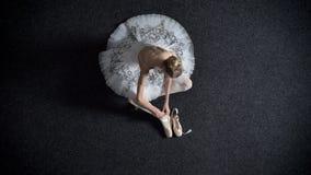 Η σκιαγραφία του ballerina νέων κοριτσιών φορά pointe, καθμένος στο πάτωμα, έννοια μπαλέτου, τοπ πυροβολισμός φιλμ μικρού μήκους