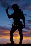 Η σκιαγραφία του cowgirl που κρατά ψηλά την πλευρά πυροβόλων όπλων κοιτάζει κάτω Στοκ φωτογραφία με δικαίωμα ελεύθερης χρήσης