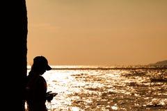 Η σκιαγραφία των νέων γυναικών χρησιμοποιεί το κινητό τηλέφωνο κοντά στην παραλία , Στοκ Εικόνες