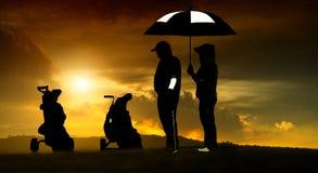 Η σκιαγραφία των παικτών γκολφ χτύπησε το σκούπισμα και κρατά το γήπεδο του γκολφ το καλοκαίρι για χαλαρώνει το χρόνο Στοκ Εικόνες