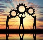 Η σκιαγραφία των τριών ατόμων που κρατούν τα εργαλεία τους έβαλε μαζί σε ένα εργαλείο Στοκ Φωτογραφίες