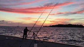Η σκιαγραφία ψαράδων στο ηλιοβασίλεμα πετά μια ράβδο αλιείας απόθεμα βίντεο