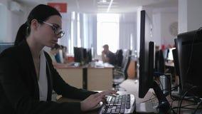 Η σκληρή εργασία γραφείων, ματαιωμένο επιχειρησιακό κορίτσι με τα γυαλιά χρησιμοποιεί τον υπολογιστή και κάνει τις σημειώσεις απόθεμα βίντεο