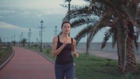 Η σκληραγωγημένη γυναίκα τρέχει μόνο στο πάρκο το βράδυ, αναπνέοντας το καθαρό αέρα απόθεμα βίντεο