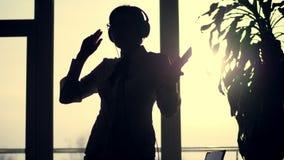 Η σκοτεινή σκιαγραφία της επιχειρησιακής γυναίκας, χοροί με τα ακουστικά και κινητός στο χέρι της, ακούει μουσική, στο κλίμα φιλμ μικρού μήκους
