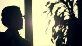Η σκοτεινή σκιαγραφία της επιχειρησιακής γυναίκας, χοροί με τα ακουστικά και κινητός στο χέρι της, ακούει μουσική, στο κλίμα απόθεμα βίντεο