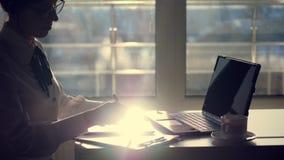 Η σκοτεινή σκιαγραφία της νέας προσεκτικής επιχειρηματία που φορά τα γυαλιά, γράφει κάτι στην ταμπλέτα, είναι έπειτα ένα lap-top απόθεμα βίντεο