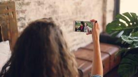 Η σκοτεινός-μαλλιαρή ομιλία γυναικών στους θηλυκούς φίλους on-line με το smartphone, κορίτσι εξετάζει την οθόνη, κρατώντας τη συσ απόθεμα βίντεο