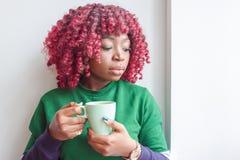 Η σκοτεινός-ξεφλουδισμένη γυναίκα έντυσε στα περιστασιακά ενδύματα κρατώντας το φλυτζάνι του ζεστού ποτού, απολαμβάνοντας τον καφ στοκ φωτογραφίες