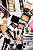 Η σκόνη, κοκκινίζει, highlighter, χρωστικές ουσίες, ακτινοβολεί, βούρτσες, nude σκιά ματιών, μαξιλάρι και eyeliner Στοκ εικόνα με δικαίωμα ελεύθερης χρήσης