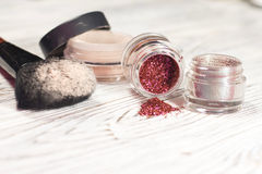 Η σκόνη, χρωστικές ουσίες, ακτινοβολεί, βούρτσες και eyeliner στοκ φωτογραφία