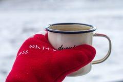 Η σμαλτωμένη κούπα με το καυτό τσάι παραδίδει ένα κόκκινο θερμό γάντι το χειμώνα σε ένα χιονώδες υπόβαθρο Στοκ Εικόνα