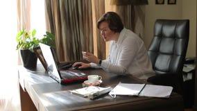 Η σοβαρή γυναίκα εξετάζει τον υπολογιστή στο Υπουργείο Εσωτερικών φιλμ μικρού μήκους