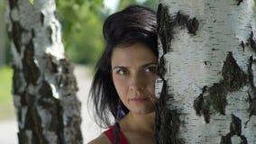 Η σοβαρή γυναίκα κοιτάζει στη σε αργή κίνηση, σκοτεινή μαλλιαρή ομορφιά πάρκων κοντά στο δέντρο, λυπημένο θηλυκό φιλμ μικρού μήκους