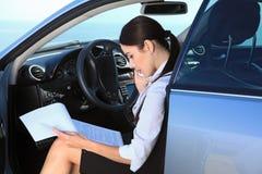 Η σοβαρή επιχειρησιακή γυναίκα στο αυτοκίνητο εξετάζει τα σημαντικά έγγραφα Στοκ Φωτογραφίες