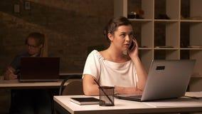 Η σοβαρή καυκάσια επιχειρηματίας έχει τη τηλεφωνική συνομιλία εξετάζοντας τον υπολογιστή της, καθμένος στον εργασιακό χώρο με απόθεμα βίντεο
