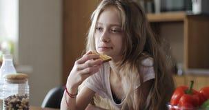 Η σοβαρή μαθήτρια με μακρυμάλλη τρώει το άσπρο ψωμί απόθεμα βίντεο
