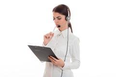 Η σοβαρή νέα εργασία επιχειρησιακών γυναικών στο τηλεφωνικό κέντρο με τα ακουστικά και το μικρόφωνο καθιστούν τις σημειώσεις απομ Στοκ φωτογραφίες με δικαίωμα ελεύθερης χρήσης