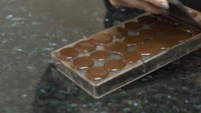 Η σοκολάτα διαγράφεται από το πιάτο ψησίματος με spatula, κλείνει επάνω φιλμ μικρού μήκους