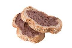 Η σοκολάτα κρεμώδης που διαδίδει καφετιά ολόκληρη στη φέτα ψωμιού σίτου απομονώνει Στοκ Φωτογραφίες
