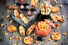 Η σοκολάτα cupcakes ` κτυπά τα δάχτυλα ` μαγισσών ` s μπισκότων ` ` και κουλουρακιών - εύγευστα γλυκά αρτοποιείων για τον εορτασμ Στοκ εικόνες με δικαίωμα ελεύθερης χρήσης