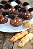 Η σοκολάτα cupcakes ` κτυπά τα δάχτυλα ` μαγισσών ` s μπισκότων ` ` και κουλουρακιών - εύγευστα γλυκά αρτοποιείων για τον εορτασμ Στοκ Φωτογραφία