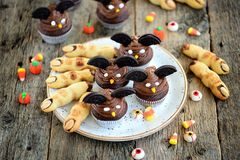 Η σοκολάτα cupcakes ` κτυπά τα δάχτυλα ` μαγισσών ` s μπισκότων ` ` και κουλουρακιών - εύγευστα γλυκά αρτοποιείων για τον εορτασμ Στοκ φωτογραφίες με δικαίωμα ελεύθερης χρήσης