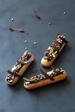 Η σοκολάτα eclairs με τα καρύδια στοκ εικόνα