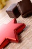Η σοκολάτα χωρίζει σε τετράγωνα με την κόκκινη μορφή αστεριών Στοκ Φωτογραφία