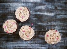 Η σοκολάτα cupcakes που διακοσμήθηκε με την κρέμα αυξήθηκε καρδιές Στοκ Εικόνες