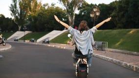 Η σπάνια άποψη μιας νεολαίας συνδέει την οδήγηση ενός ηλεκτρικού ποδηλάτου στο πράσινο πάρκο Το κορίτσι σε ένα μπλε πουκάμισο με  απόθεμα βίντεο
