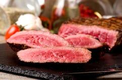 Η σπάνια μπριζόλα βόειου κρέατος τεμάχισε το μαύρο πιάτο στοκ εικόνα