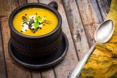 Η σπιτικά κολοκύθα και το καρότο αποβουτυρώνουν τη σούπα με το τυρί φέτας, το μαύρους σουσάμι και τους σπόρους κολοκύθας Στοκ Φωτογραφία