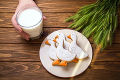 Η σπιτική πάπια μπισκότων πιπεροριζών διαμόρφωσε και ποτήρι του γάλακτος στον ξύλινο πίνακα με το αυτί του σίτου με τον ανθρώπινο Στοκ φωτογραφίες με δικαίωμα ελεύθερης χρήσης