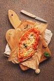 Η σπιτική πίτσα με τα μανιτάρια, η ντομάτα και το τυρί σε μια κοπή επιβιβάζονται, καφετί υπόβαθρο πετρών Η τοπ άποψη, επίπεδη βάζ στοκ φωτογραφία με δικαίωμα ελεύθερης χρήσης