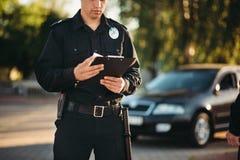 Η σπόλα με το σημειωματάριο στα χέρια ελέγχει το αυτοκίνητο στοκ φωτογραφίες