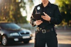 Η σπόλα με το σημειωματάριο στα χέρια ελέγχει το αυτοκίνητο στοκ εικόνες με δικαίωμα ελεύθερης χρήσης