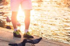 Η στάση αθλητικών παπουτσιών ένδυσης ατόμων κοντά στον ποταμό και το ελαφρύ ηλιοβασίλεμα Στοκ Εικόνες
