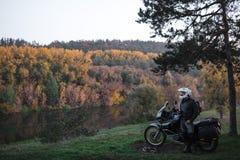 Η στάση αναβατών με τη μοτοσικλέτα περιπέτειας, εργαλείο μοτοσυκλετιστών, οδηγός μοτοσικλετών Α κοιτάζει, έννοια του ενεργού τρόπ στοκ εικόνα