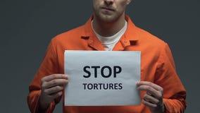 Η στάση βασανίζει τη φράση στο χαρτόνι στα χέρια του καυκάσιου φυλακισμένου, διαμαρτυρία απόθεμα βίντεο