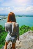 Η στάση γυναικών στον απότομο βράχο και βλέπει κάτι στο μπλε ουρανό, την μπλε θάλασσα και το σύννεφο Στοκ Φωτογραφία