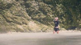 Η στάση γυναικών τουριστών στη λίμνη βουνών κάτω από το νερό ρίχνει την πτώση από τον καταρράκτη στην ευτυχή απόλαυση γυναικών τρ απόθεμα βίντεο