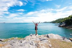 Η στάση γυναικών τρόπου ζωής χαλαρώνει σε έναν βράχο επάνω από τον ωκεανό Στοκ Εικόνες