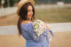 Η στάση γυναικών Georgeus μπροστά από το αγρόκτημα και κρατά μια ανθοδέσμη του λουλουδιού στα χέρια Ανθοδέσμη Beautuful Γυναίκα σ στοκ εικόνες
