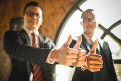 Η στάση δύο επιχειρηματιών και παρουσιάζει στον αντίχειρα χέρι τους στην επίδειξη της συμφωνίας τους για να υπογράψει τη συμφωνία Στοκ Φωτογραφία