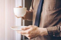 Η στάση επιχειρηματιών κοντά στο παράθυρο και το κράτημα του φλυτζανιού καφέ χαλαρώνουν εργαζόμενων Στοκ Φωτογραφίες